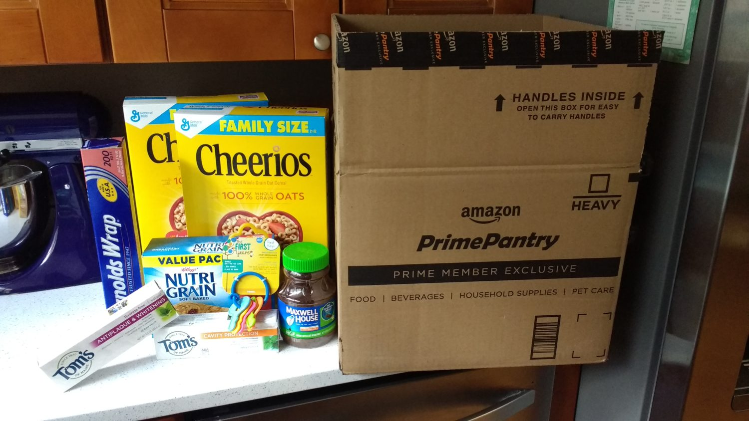 Amazon Prime Pantry box with Cheerios, Reynolds Wrap, Tom's of Maine, Maxwell House, Nutri-Grain, and teether keys