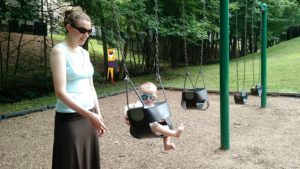2017 Stephonee with baby in a park swing, mysterious benefactor lurking in the background looking shady