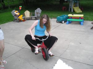 Stephonee in 2007, riding a child's tricycle, mysterious benefactor in background lounging in adirondack chair with a drink